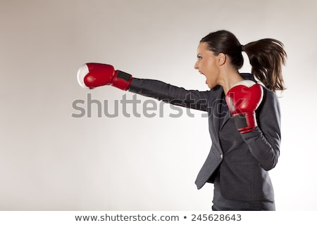Stock photo: Kicking businesswoman with boxing gloves