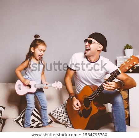 Stock photo: Man looking girl playing guitar