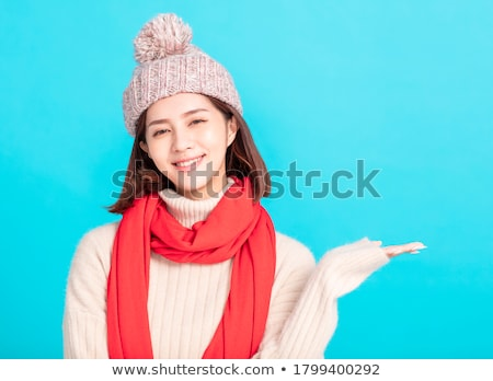 Young woman in warm clothing and showing something Stock photo © bmonteny