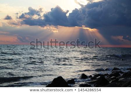 Sun's Last Orange Rays through the Clouds at Dusk Stock photo © pzaxe