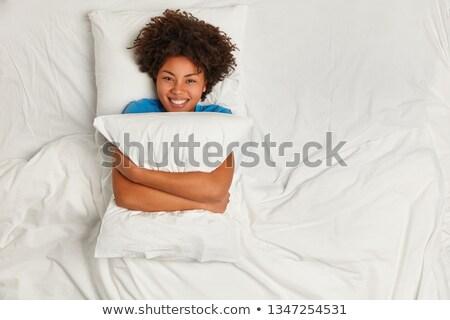улыбающаяся женщина кровать подушкой улыбаясь красивой Сток-фото © deandrobot