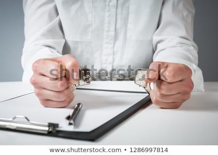 Female hands cuffed, top view of police investigator desk Stock photo © stevanovicigor