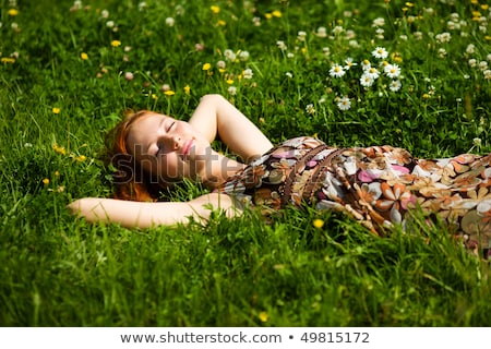 Portrait of a young redhead woman lying down on green spring gra Stock photo © Massonforstock