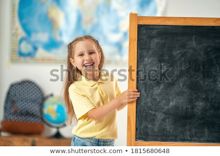 Schoolgirl standing against blackboard in classroom Stock photo © wavebreak_media