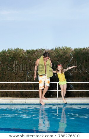 Father and girl dipping toes in pool Stock photo © IS2