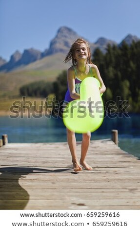 Girl playing with pool toy on jetty Stock photo © IS2