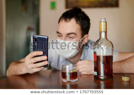 drunk man with alcohol and smartphone at home Stock photo © dolgachov
