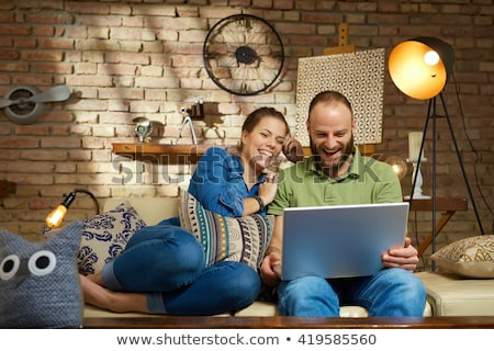 Joyous young man sitting on sofa in living room and laughing, wh Stock photo © deandrobot