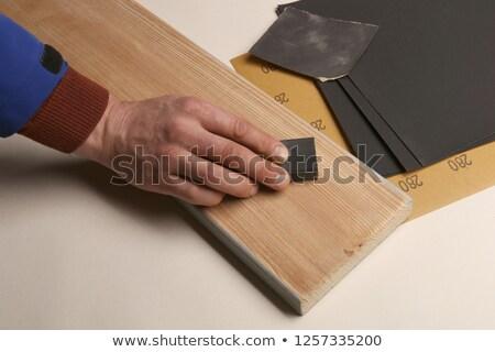 Carpenter sanding piece of wood by hand Stock photo © Kzenon