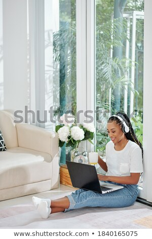 Young female with dreadlocks sitting on the floor in one of yoga positions Stock photo © pressmaster