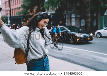 Headphones young woman walking in new york city using phone app listening to podcast or audiobook wi Stock photo © Maridav