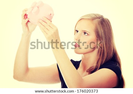 Young happy business woman putting money in the piggybank and dr stock photo © HASLOO