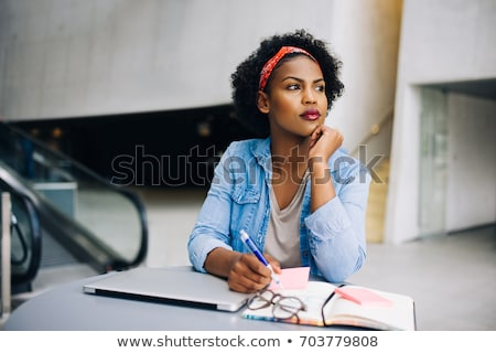 thoughtful young african american woman thinking and writing in notebook stock photo © deandrobot