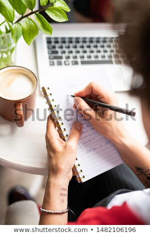 Young female manager making notes in notebook while organizing work Stock photo © pressmaster