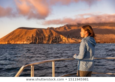 Cruise ship tourist on boat looking at sunset landscape in Galapagos Islands Stock photo © Maridav