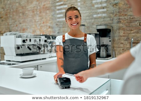 Young client of cafe paying for food or drink by contactless payment Stock photo © pressmaster