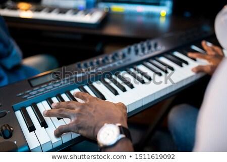Handen jonge afrikaanse muzikant aanraken sleutels Stockfoto © pressmaster