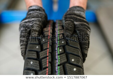 New tyre for car or lorry held by worker of contemporary machine repair service Stock photo © pressmaster