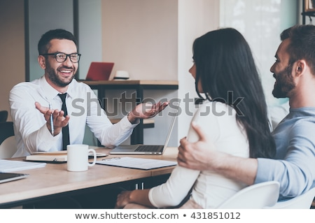 Young cheerful financial advisor or agent consulting mature husband and wife Stock photo © pressmaster