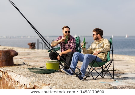 happy friends with fishing rods and beer on pier Stock photo © dolgachov