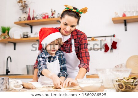 Cute little boy in Santa cap and his mother making gingerbread cookies Stock photo © pressmaster