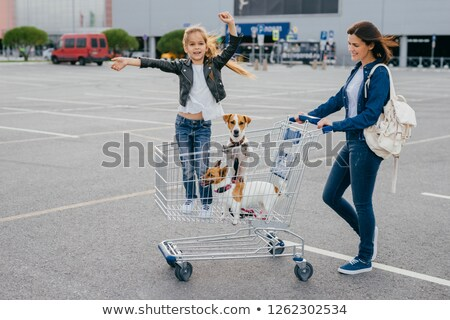 Shopping and family concept. Glad female carries trolley in which little girl stands with dogs, pose Stock photo © vkstudio