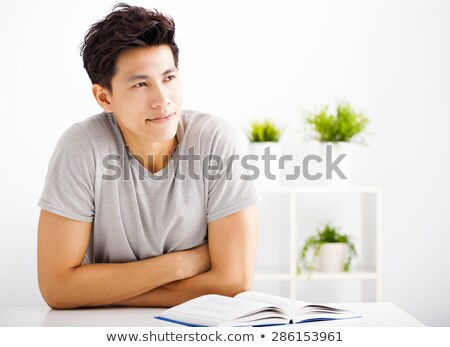portrait of a young handsome man with a book indoors stock photo © hasloo