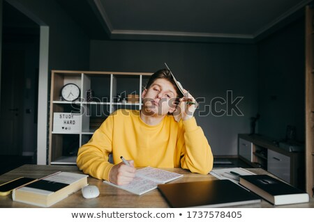 Young teenager writing in his notebook in living room  stock photo © get4net