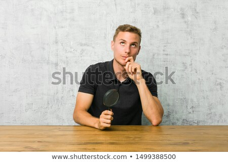 young man looking up with a magnifying glass stock photo © get4net