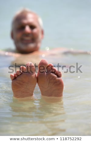 Man poking his feet out of the water Stock photo © photography33