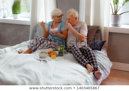 Good looking woman eating cereals in her bedroom Stock photo © wavebreak_media