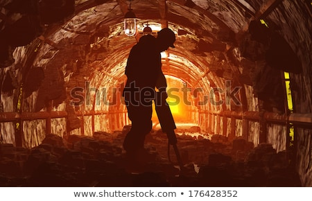 Stok fotoğraf: Silhouette Of A Mine Worker With Helmet