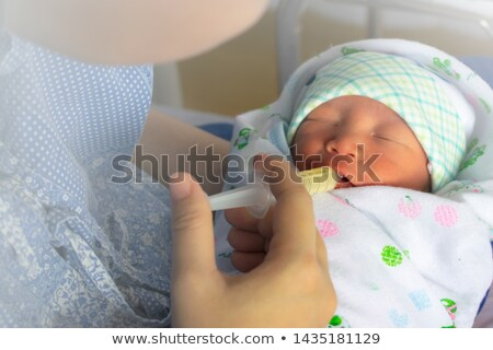 mother feeding newborn baby milk with syringe stock photo © photobac