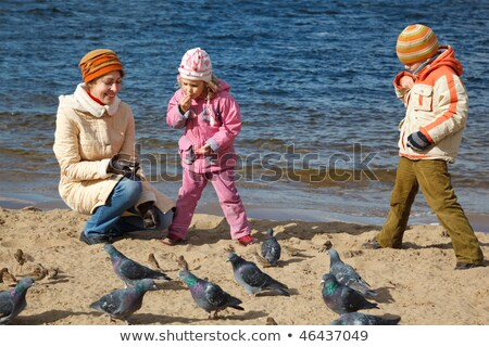 Boy and girl together with mum feed birds on autumn beach. Productive leisure in open air. Stock photo © Paha_L
