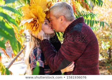 Old man and old woman with wreath of maple leaves kissing in autumnal forest Stock photo © Paha_L