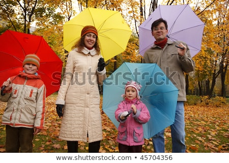 Family from four persons in autumn park with multi-coloured umbrellas. Stock photo © Paha_L