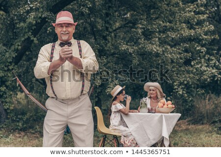 Grandmother with grandfather behind table with grandson and granddaughter