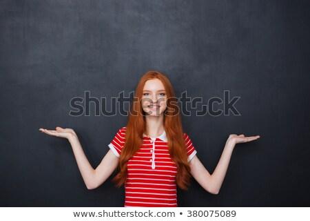 Cheerful woman holding copyspace on both palms over chalkboard background Stock photo © deandrobot