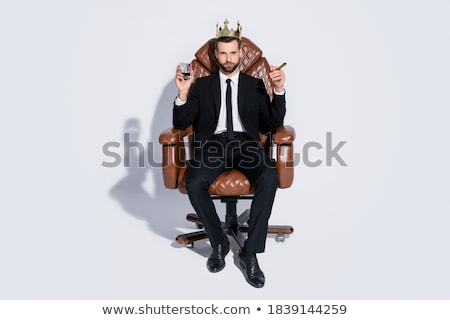 confident handsome businessman sitting in office chair and smoking cigar stock photo © deandrobot