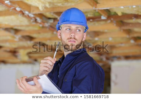 Builder in hardhat with clipboard and pencil indoors Stock photo © deandrobot