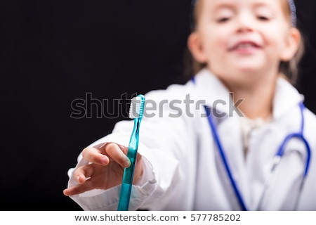 little girl holding out a toothbrush to the viewer stock photo © giulio_fornasar