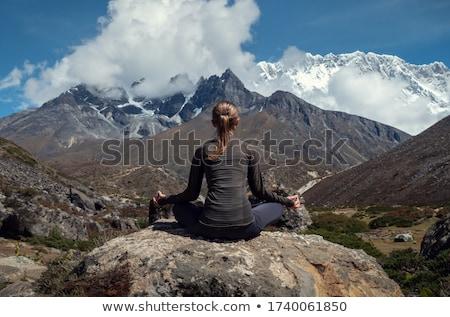 Beautiful woman sitting on mountain top and contemplating landsc Stock photo © Yatsenko
