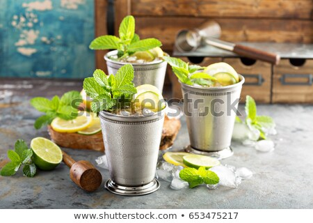 Mint Julep cocktail with bourbon, ice and mint in glass on black background stock photo © yelenayemchuk