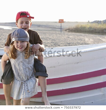 Girl giving piggyback to boy by boat Stock photo © IS2