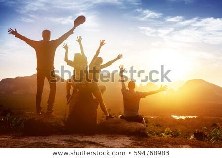 young woman with raised up arms on the mountain peak stock photo © denbelitsky
