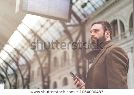 busy bearded man in business clothes talking by smartphone stock photo © deandrobot