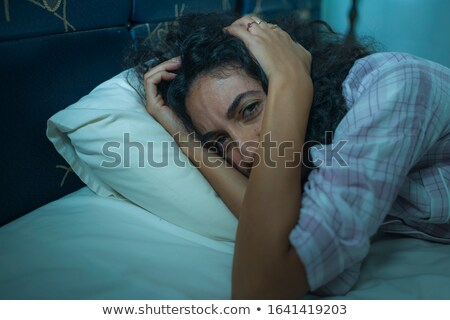 A Middle Eastern woman lying on a bed Stock photo © monkey_business