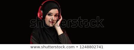 Portrait of beautiful smart young muslim woman wearing black hijab listening to music in headphones  Stock photo © Traimak