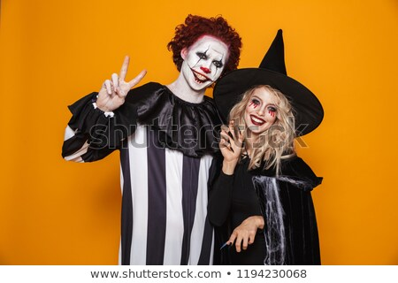 Smiling woman witch and clown looking camera and smiling isolated Stock photo © deandrobot