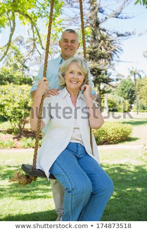 couple of senior woman and man sitting in a meadow in the grass stock photo © kzenon
